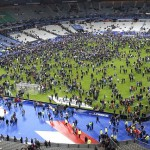 Supporters gather on the pitch at the end of the game ahead of being evacuated from the Stade de France – © Image: AP