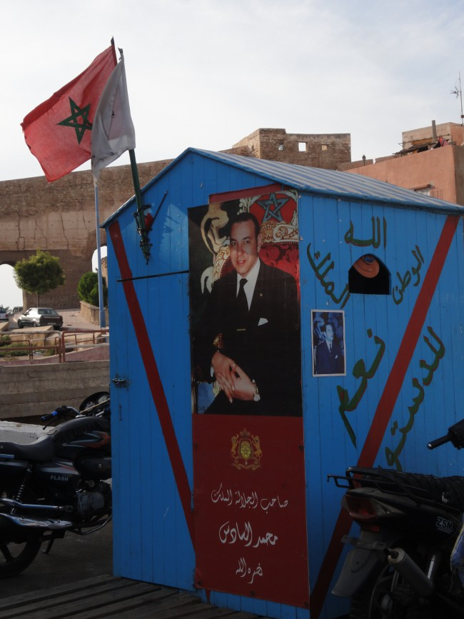 King of Morocco Mohammad the sixth in a poster on an old hut. It translates, Allah, the country and the King – Yes to the constitution.