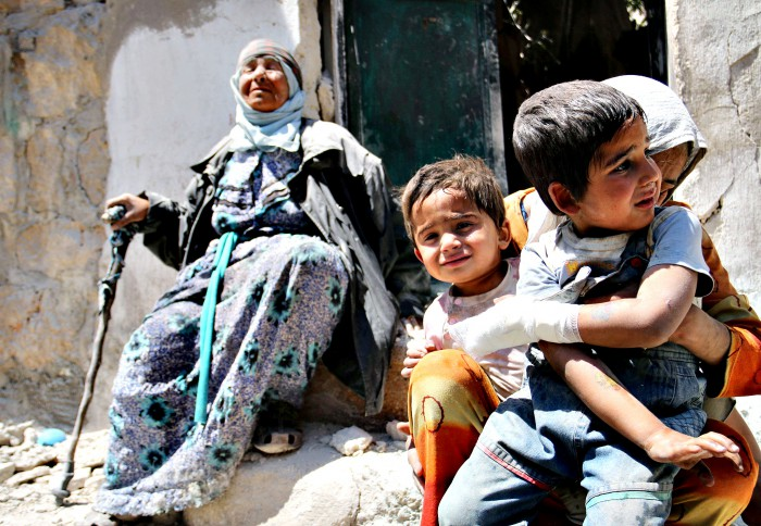 A Syrian woman comforts her children after their house in the northern Syrian city of Aleppo was bombed by forces loyal to the Syrian regime. MPC Journal, Zein Al-Rifei/AFP