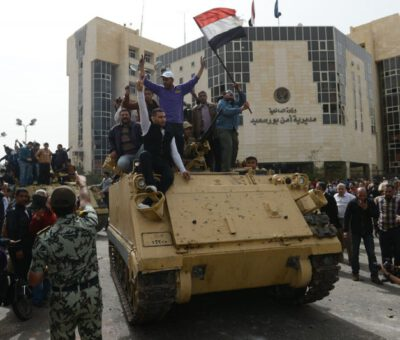 Egyptian protesters hold their national flag as they celebrate on an army tank outside Port Said's security headquarters on March 8, 2013, following the withdrawal of police forces from their headquarters in the Suez Canal city that has been the target of protesters and transferred its protection to the military, the interior ministry said. © Image: Khaled Desouki/AFP/Getty Images, MPC Journal