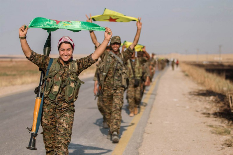 Kurdish fighters carry their flags celebrating victory in Tel Abyad. @ Image: Reuters – Rodi Said