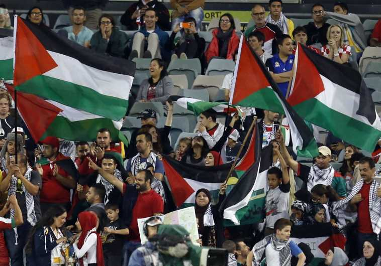 Fans of the Palestinian national team wave flags during their Asian Cup soccer match against Iraq – © Image: REUTERS. MPC Journal