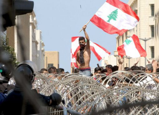 Lebanese protesters wave the national flag in front of a barbed wire fence during a demonstration in the capital Beirut – © Image: AFP: Anwar Amro