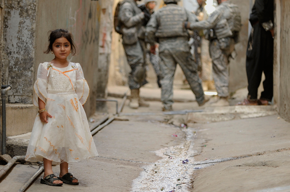 Victims of Chemical Weapons Are Soon to Be Forgotten - A girl stands outside her house in the District of Mosul, Iraq, as soldiers carry out an operation behind her. DVIDSHUB (CC BY 2.0)