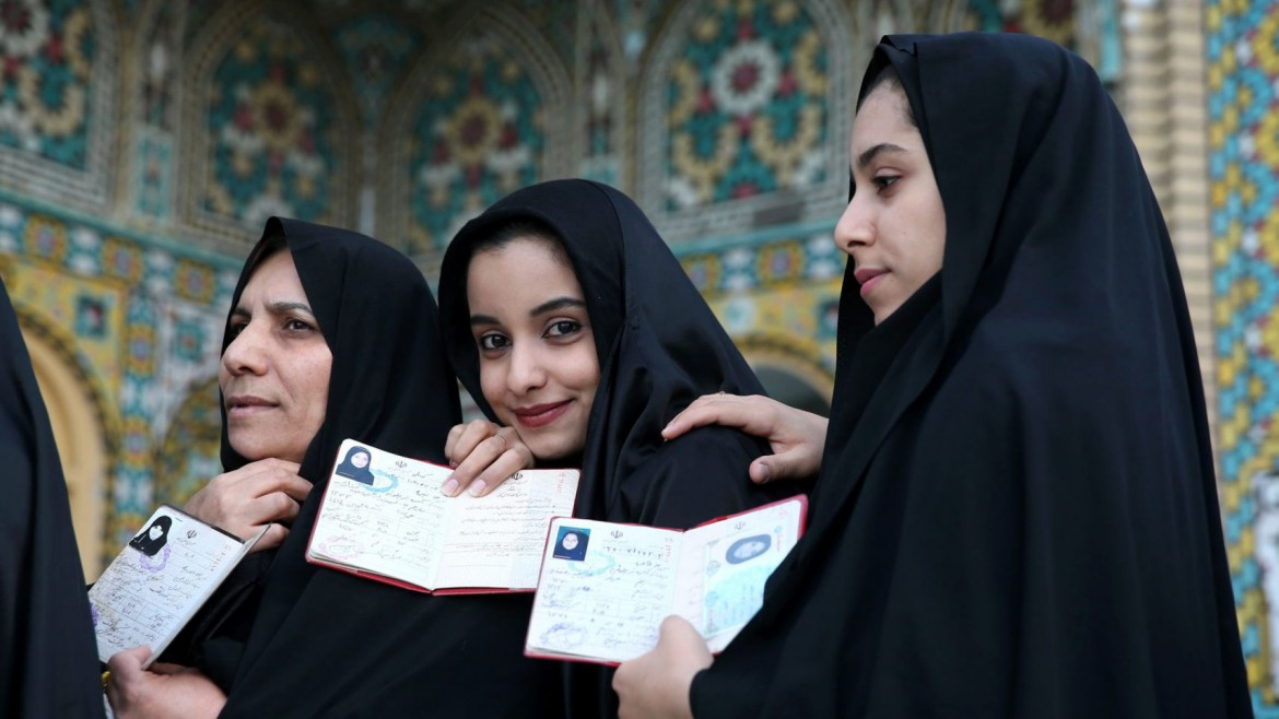 Iranian women show their identification, as they queue in a polling station to vote for the parliamentary and Experts Assembly elections in Qom.AP MPC Journal