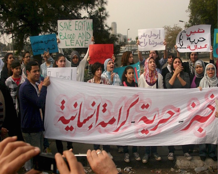 "A group of young ladies carrying a large banner saying ""bread - freedom - human dignity""[lit. khobz - huriyya - karama insaniyya] in Tahrir Square on 01 February 2011. © Image: Osama M. Hijji."