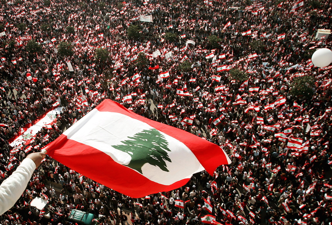 A supporter waves a Lebanese flag over thousands of anti-Syrian protesters during a rally in Beirut ..