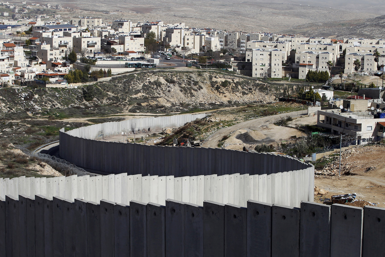 A section of the controversial Israeli barrier is seen between the Shuafat refugee camp (right) in the West Bank near Jerusalem and Pisgat Zeev (rear), in an area of Israel annexed to Jerusalem after capturing it in the 1967 Middle East war, Jan. 27, 2012. PHOTO: REUTERS/BAZ RATNER
