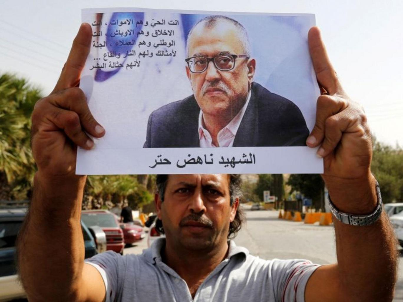 Perfect Assassination of Jordanian Writer - MPC Journal - A relative of Jordanian writer Nahed Hattar holds his picture during a sit-in in the town of Al-Fuheis near Amman, Jordan, 25 September, 2016 Reuters