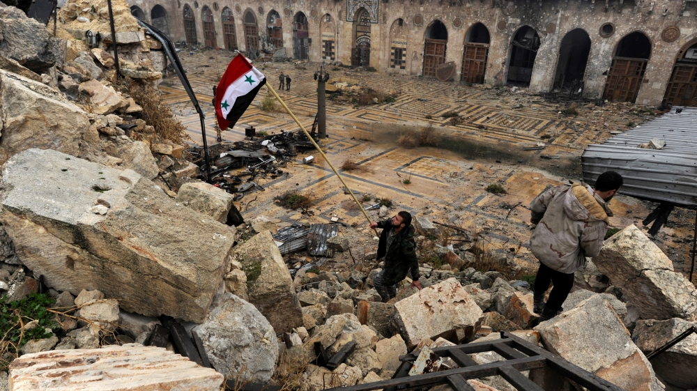 Syrian soldier with the national flag inside Aleppo's Umayyad Mosque [Reuters/Omar Sanadiki]
