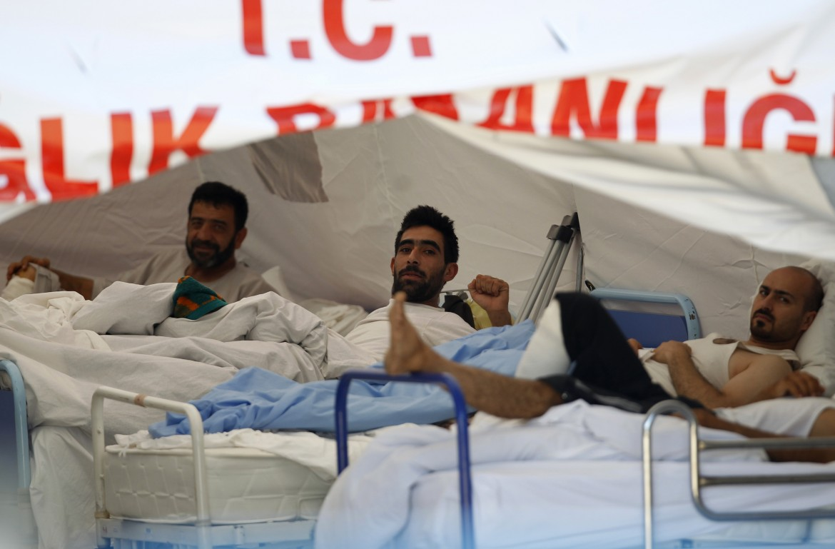 Wounded Syrian men rest in a medical tent next to a refugee camp in the Turkish border town of Yayladagi in Hatay province