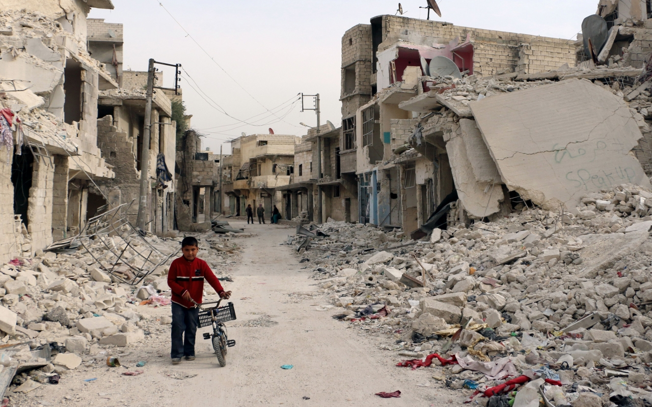 Syria Safe-Zones-Plan Takes Effect - A Syrian boy walks with his bicycle in the devastated Sukari district in the northern city of Aleppo – © Photo: Baraa Al-Halabi/AFP