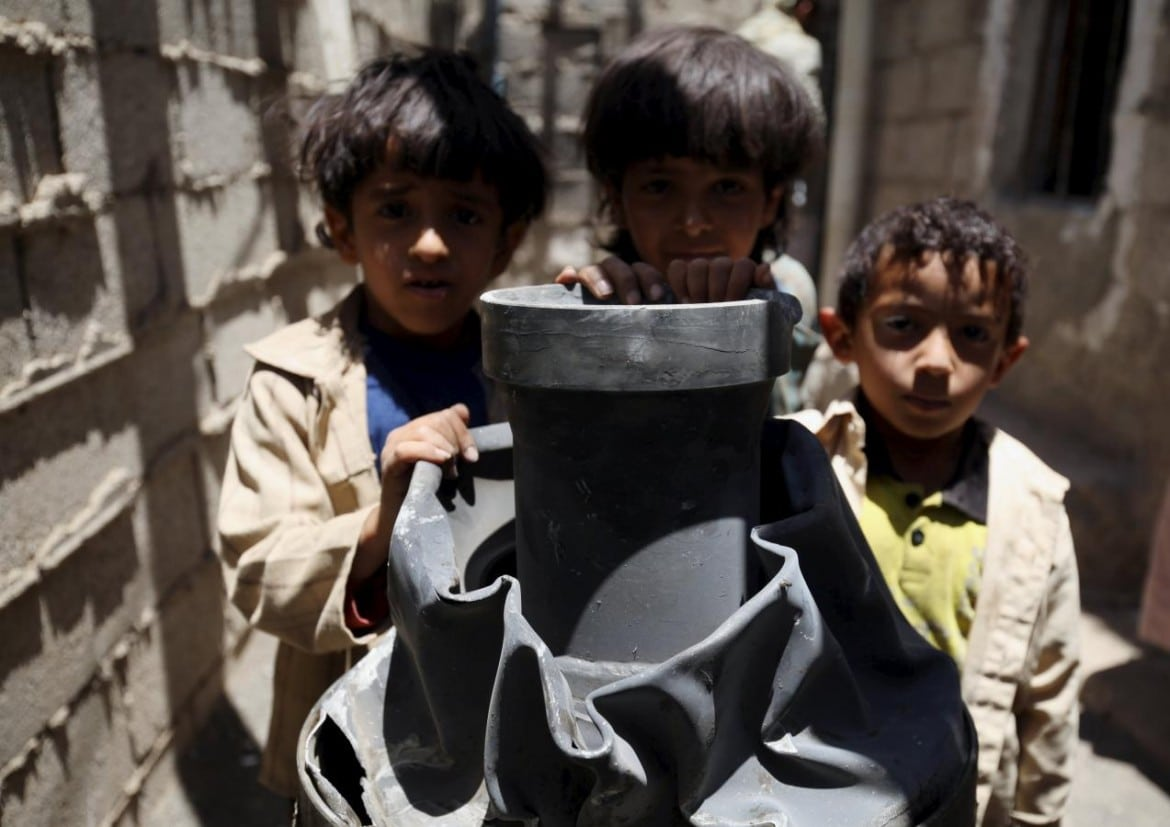 Children stand next to a shell which landed on their house from a nearby missile base after the base was struck by a Saudi-led coalition air strike, near Sanaa
