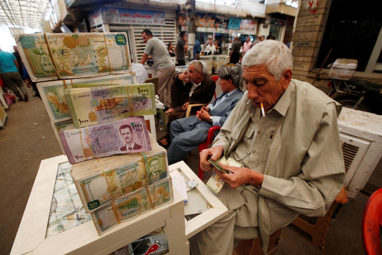 A man counts money at Stock Exchange in Erbil
