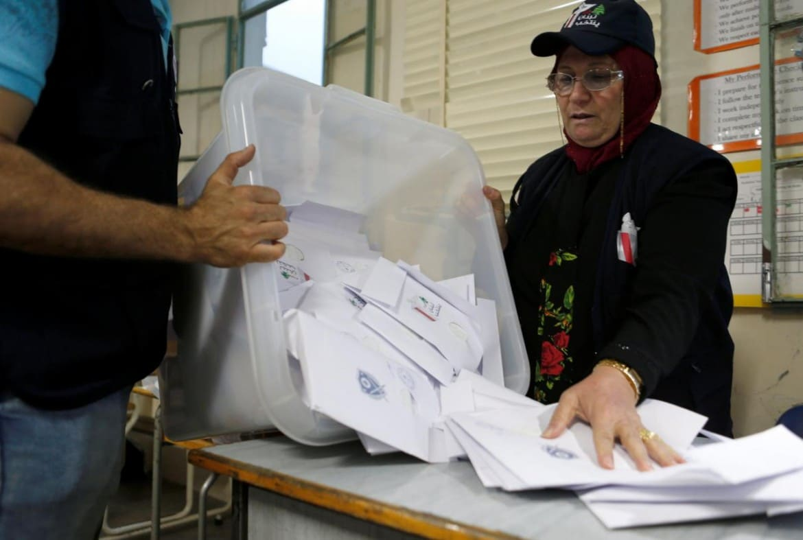 A Lebanese election official empties a ballot box after the polling station closed during Lebanon's parliamentary election, in Beirut